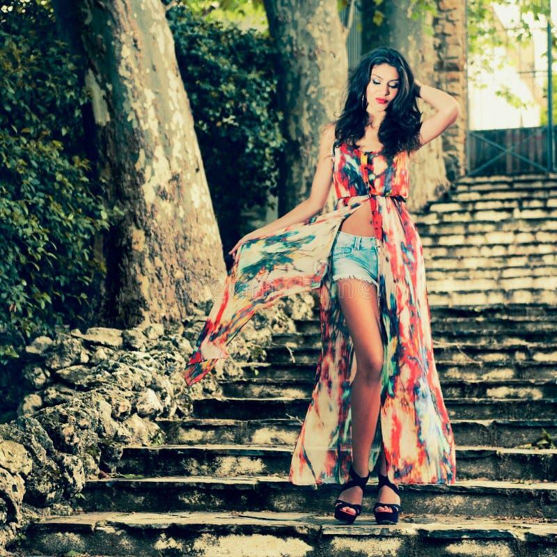 Jovem mulher bonita, modelo da forma, em escadas de um jardim fotos de stock
