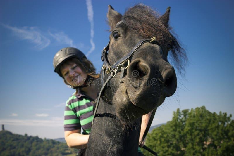 A jovem mulher bonita monta seu cavalo preto foto de stock