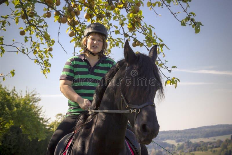 A jovem mulher bonita monta seu cavalo preto fotografia de stock royalty free