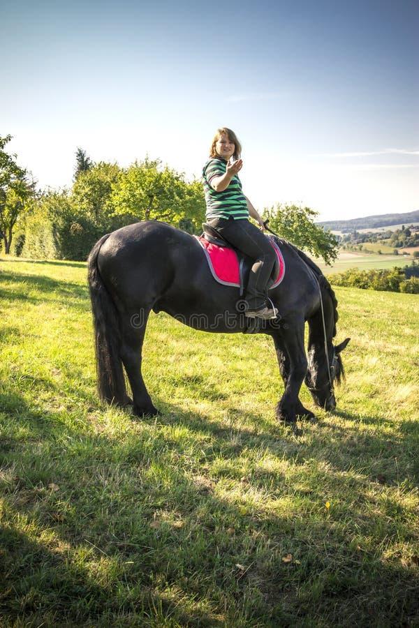 A jovem mulher bonita monta seu cavalo preto foto de stock royalty free
