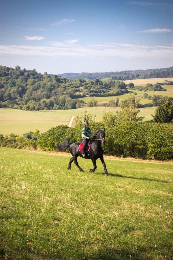 A jovem mulher bonita monta seu cavalo preto fotos de stock