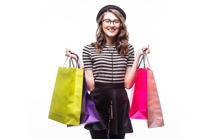 Jovem mulher bonita muito feliz na roupa ocasional com os sacos de compras isolados sobre o fundo branco imagem de stock