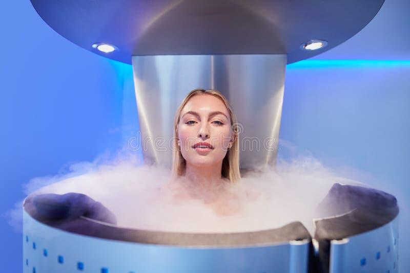 Jovem mulher bonita na cabine do cryosauna imagem de stock royalty free