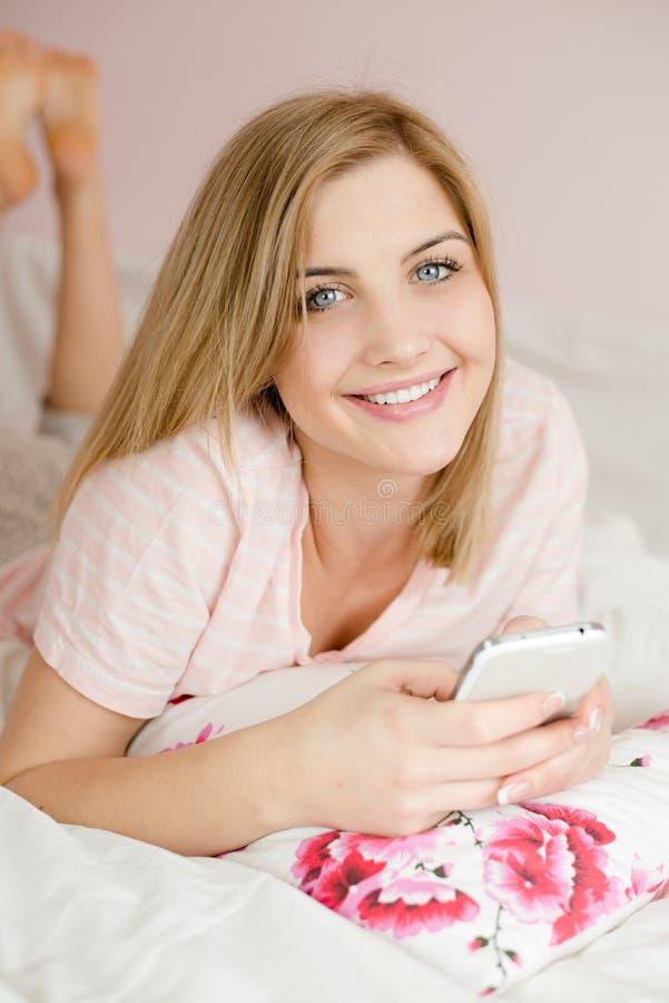 Jovem mulher bonita na cama com telefone celular fotografia de stock royalty free