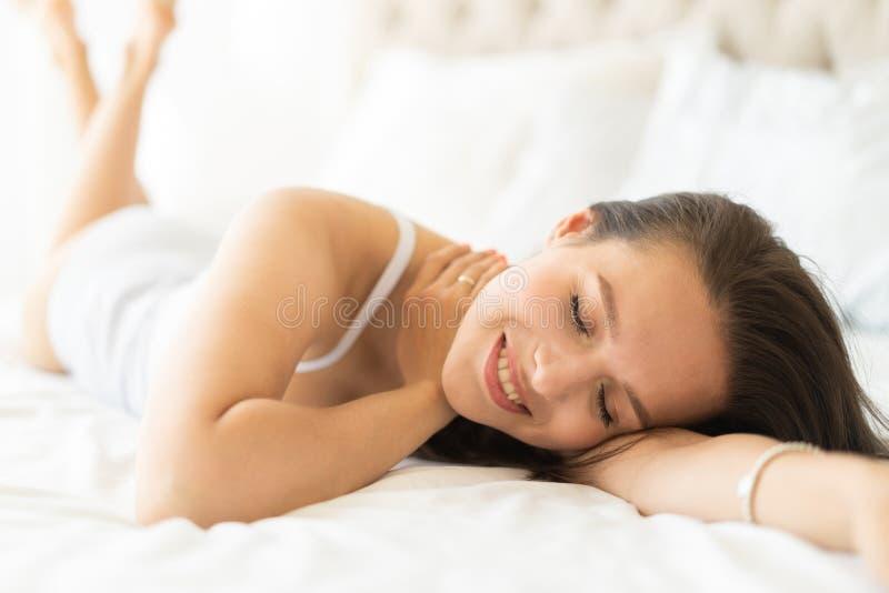 A jovem mulher bonita na cama no apartamento moderno que sorri ap?s acorda fotografia de stock