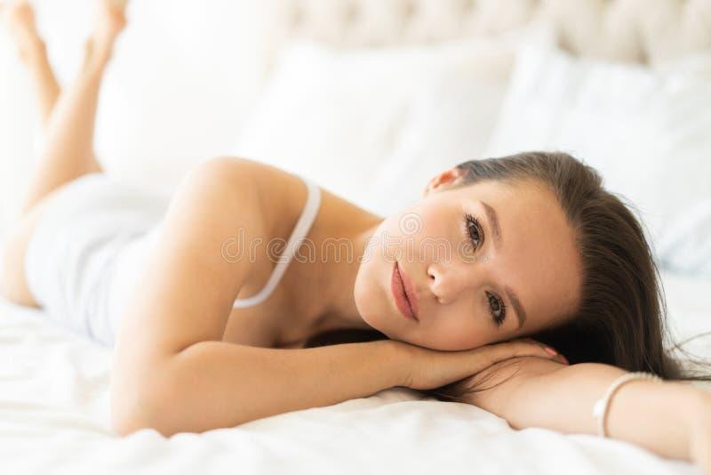 A jovem mulher bonita na cama no apartamento moderno que sorri ap?s acorda fotos de stock
