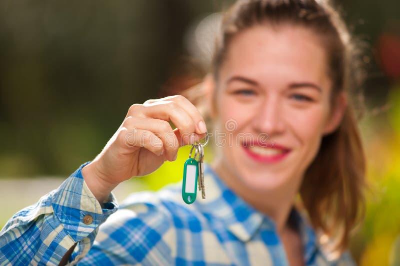 A jovem mulher bonita na camisa de manta guarda chaves imagens de stock