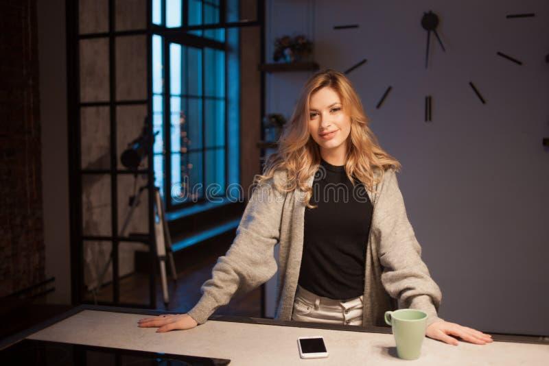 Jovem mulher bonita na cozinha, amanhecer, escuro no apartamento fotografia de stock