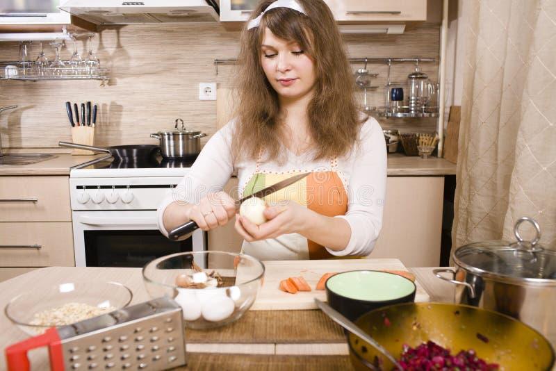 Jovem mulher bonita na cozinha que prepara o jantar fotos de stock royalty free