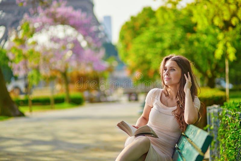 Jovem mulher bonita na leitura de Paris no banco fora fotografia de stock