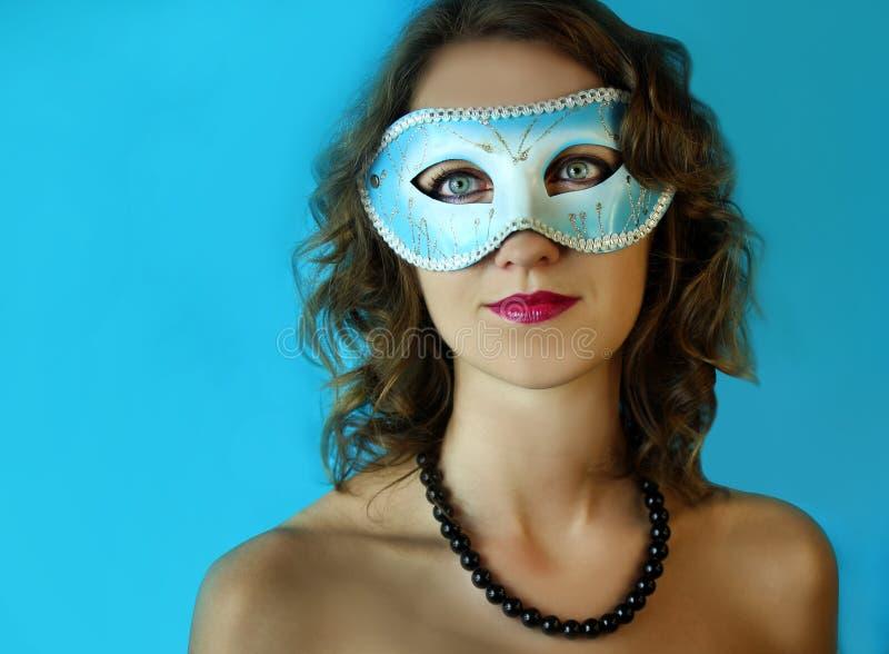 Jovem mulher bonita na máscara azul misteriosa do carnaval Foto da forma e da beleza foto de stock