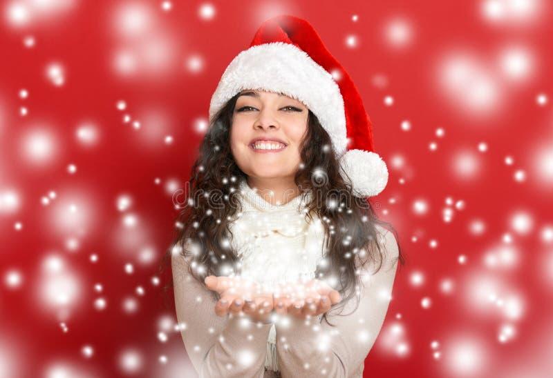Jovem mulher bonita na neve de sopro das palmas, fundo vermelho do chapéu do ajudante de Santa imagens de stock royalty free