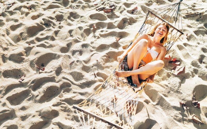 Jovem mulher bonita na parte superior de biquini que balan?a na rede no Sandy Beach e alegre rindo in camera a vista superior foto de stock