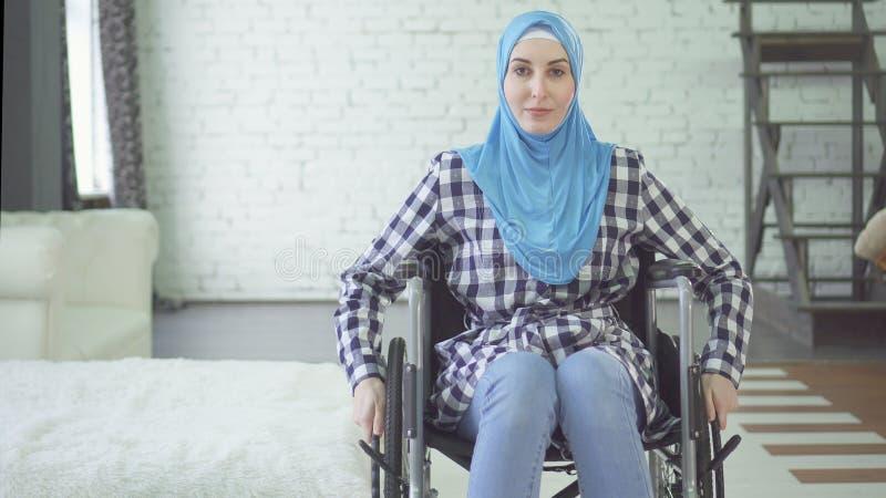 Jovem mulher bonita na pessoa deficiente do hijab, cadeira de rodas, no apartamento foto de stock royalty free