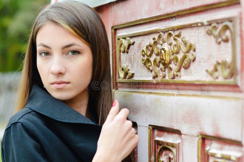 Jovem mulher bonita na porta decorada dourada imagens de stock