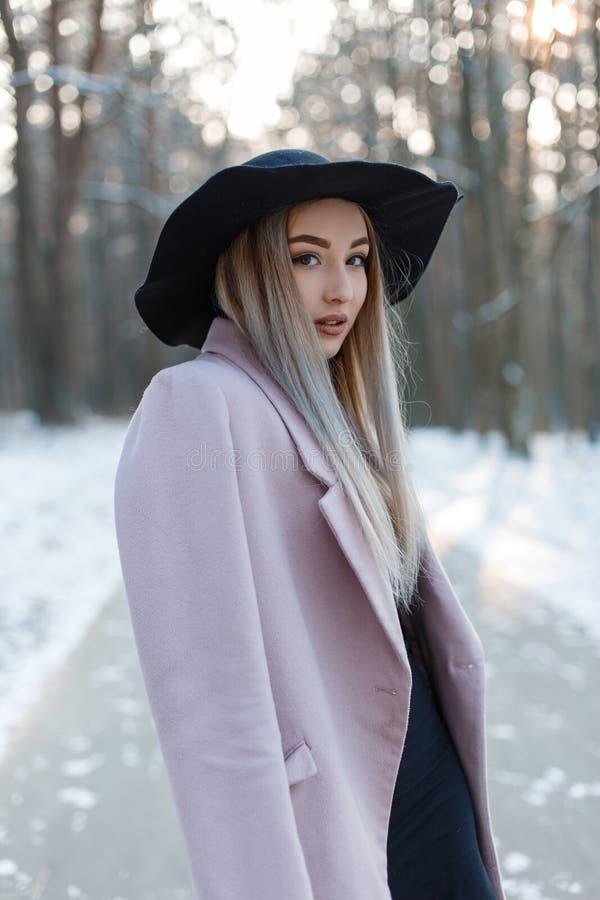 A jovem mulher bonita bonita na roupa à moda do encanto do inverno vai em um chapéu chique em uma floresta nevado em um dia ensol fotos de stock