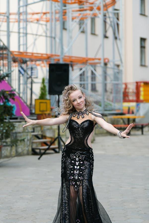 Jovem mulher bonita na roupa de um estilo ocasional isolada sobre o fundo branco Moça que dança em público, dança árabe, menina imagem de stock