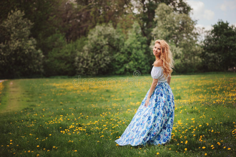 Jovem mulher bonita na saia maxi azul floral que anda na mola fotos de stock royalty free