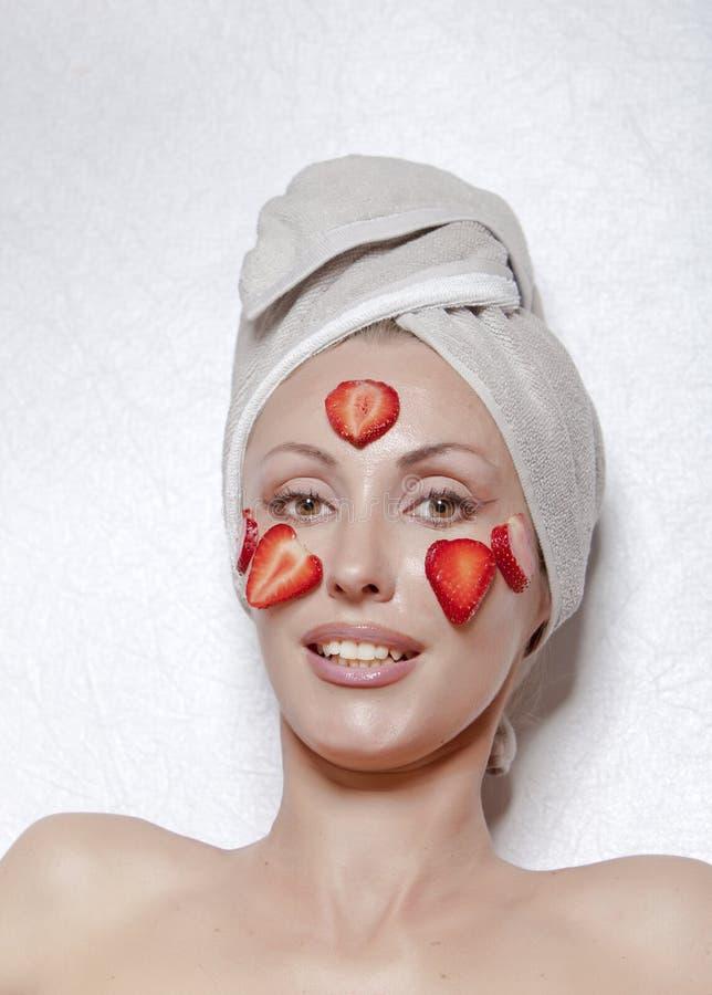 Jovem mulher bonita na toalha com uma máscara do cosmético da morango imagens de stock royalty free