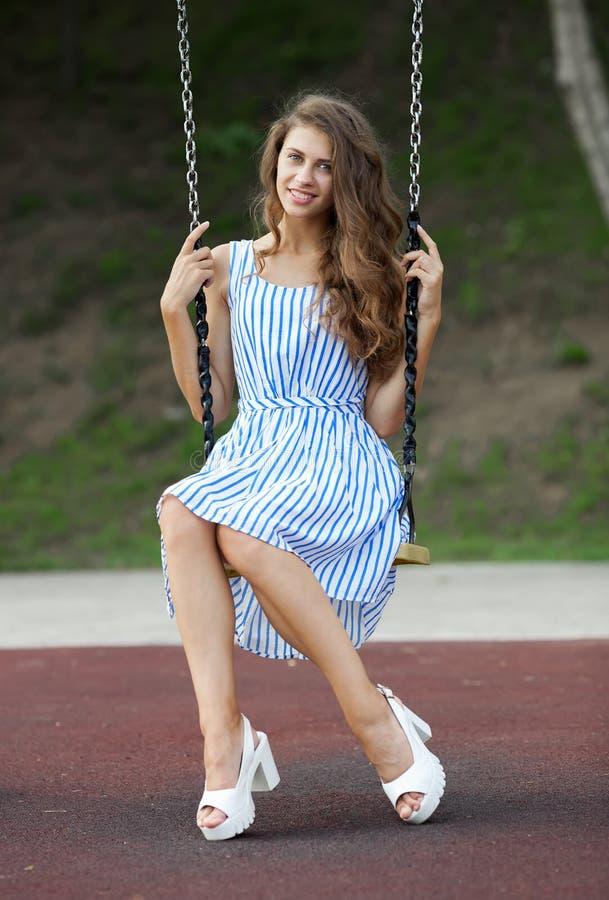 A jovem mulher bonita no azul branco listrou o vestido que tem o divertimento em um balanço no parque da cidade foto de stock royalty free