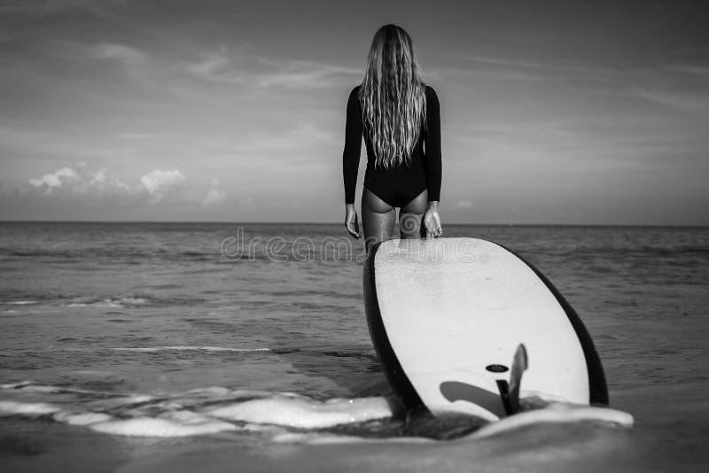 Jovem mulher bonita no biquini com placa de ressaca na praia da ilha tropical fotos de stock royalty free