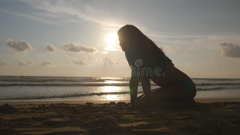 Jovem mulher bonita no biquini que senta-se na areia dourada na praia do mar durante o por do sol Menina que relaxa no paraíso pe imagem de stock royalty free