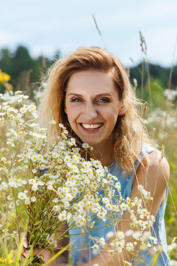 Jovem mulher bonita no campo de flores da margarida foto de stock