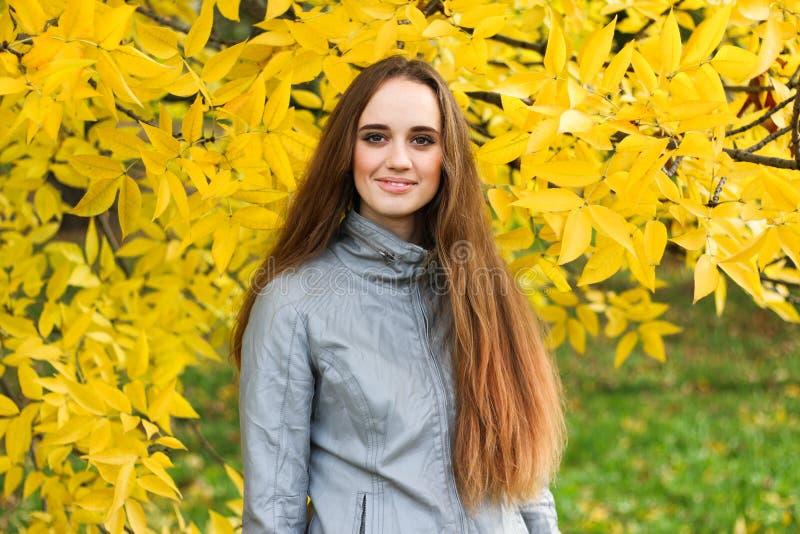 A jovem mulher bonita no casaco de cabedal e a saia preta que levanta no outono estacionam fotos de stock royalty free