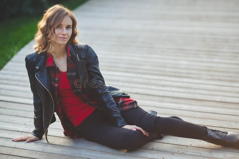 Jovem mulher bonita no casaco de cabedal preto Retrato ao ar livre foto de stock