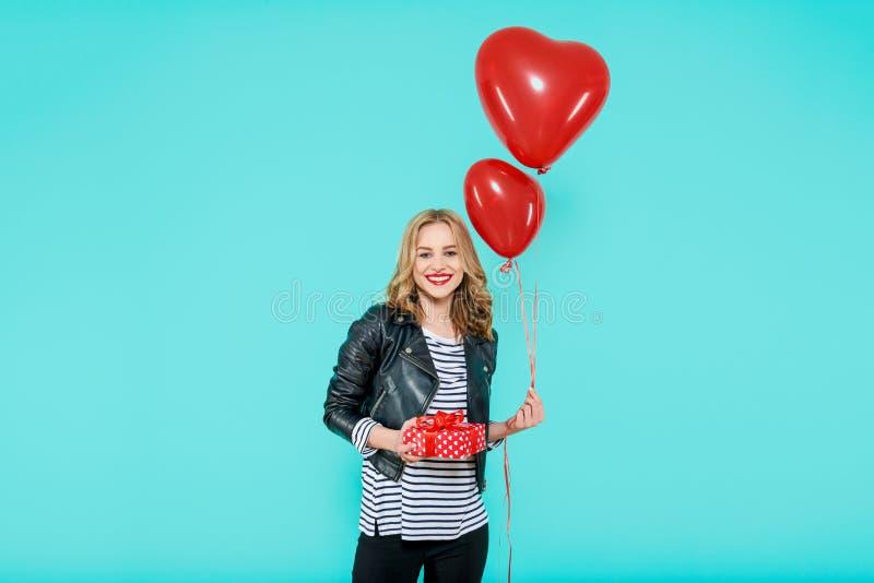 A jovem mulher bonita no casaco de cabedal que guarda o coração deu forma a balões e envolveu o presente de aniversário Conceito  fotografia de stock