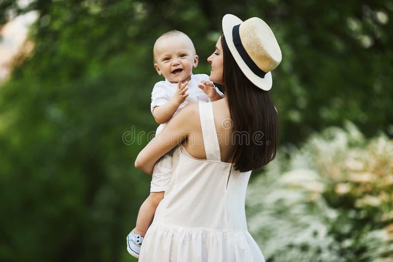 Jovem mulher bonita no chapéu à moda e em um vestido branco com seu filho pequeno bonito na camisa e no short em suas mãos foto de stock