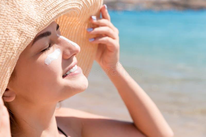 A jovem mulher bonita no chap?u est? aplicando o sunblock sob seus olhos e em seu nariz como o indiano Conceito da prote??o de Su imagens de stock royalty free
