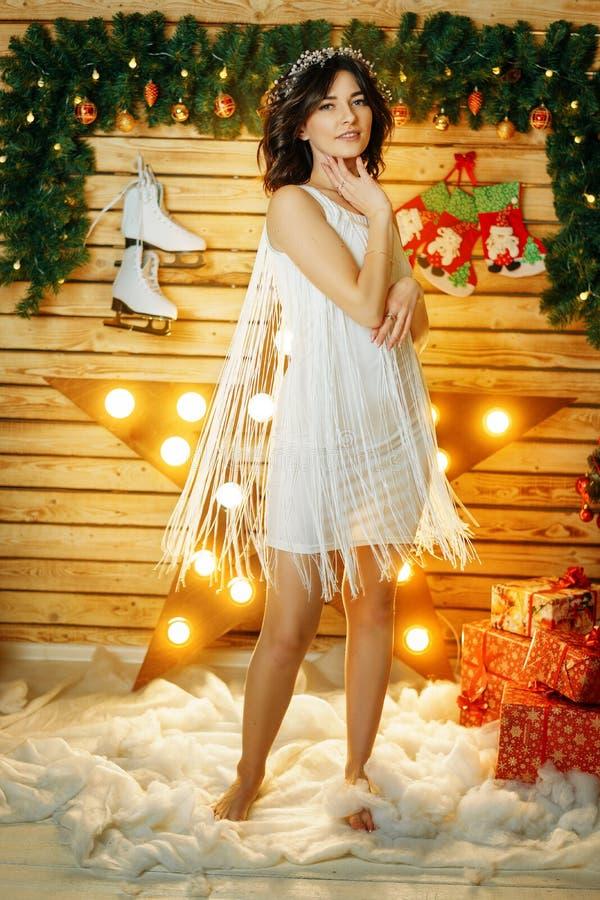 Jovem mulher bonita no fundo das luzes, humor de dança do Natal fotografia de stock royalty free