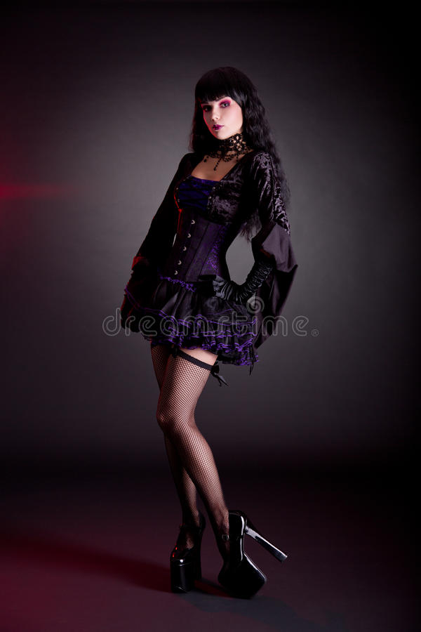 Jovem mulher bonita no outfi roxo e preto vitoriano de Dia das Bruxas fotografia de stock royalty free