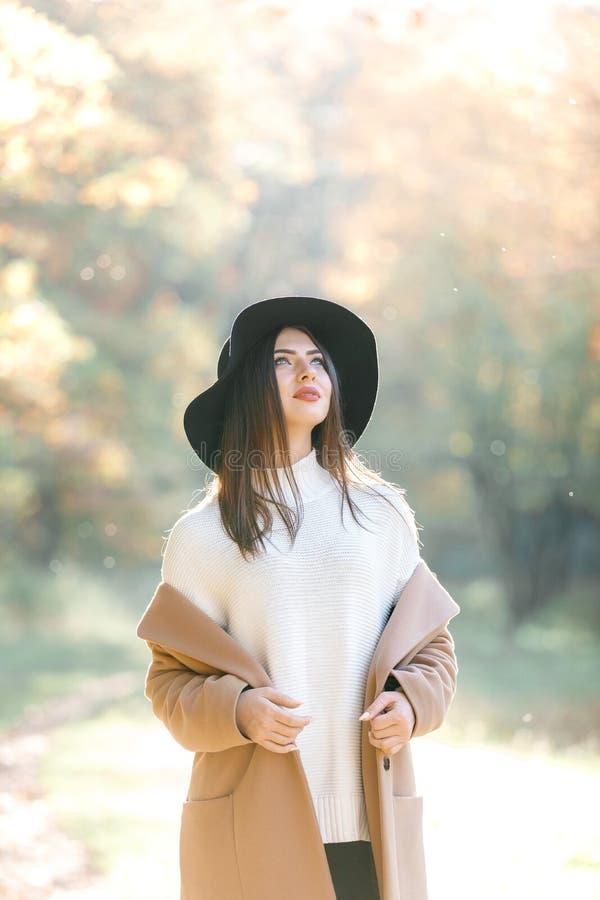 Jovem mulher bonita no revestimento e no chapéu negro no parque imagens de stock royalty free
