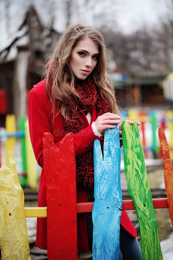 Jovem mulher bonita no revestimento vermelho e no lenço feito malha fotos de stock royalty free