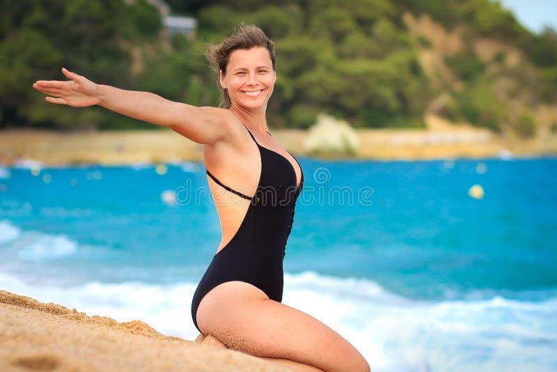 Jovem mulher bonita no roupa de banho no Sandy Beach contra o mar azul A menina feliz está tomando sol na praia foto de stock royalty free