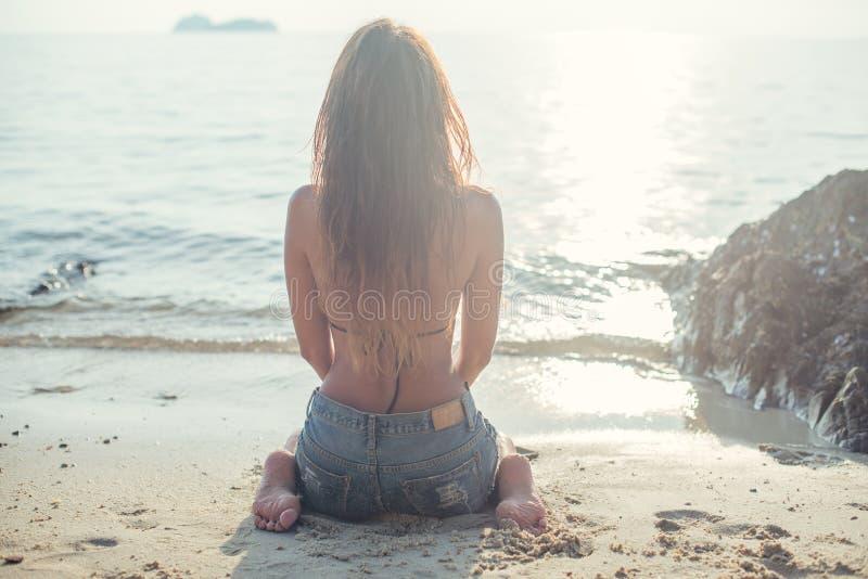 Jovem mulher bonita no short das calças de brim com descanso imagem de stock