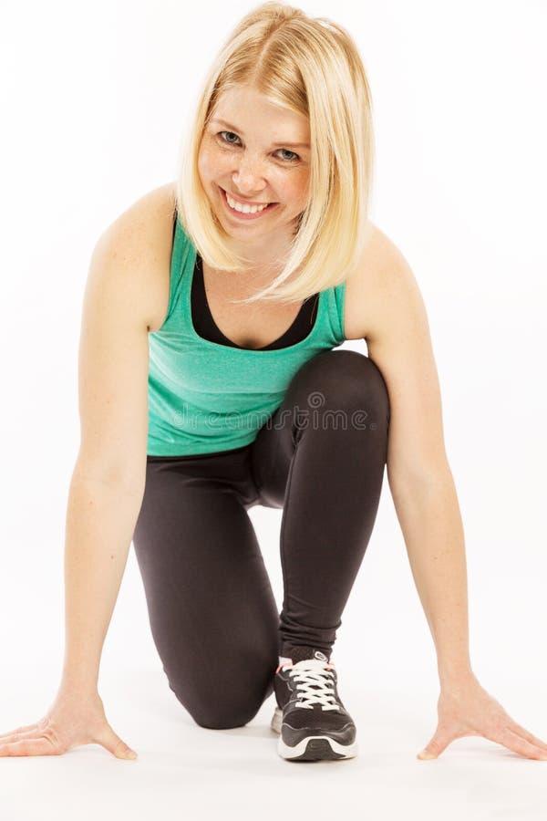 Jovem mulher bonita no sportswear brilhante em uma pose do começo imagem de stock