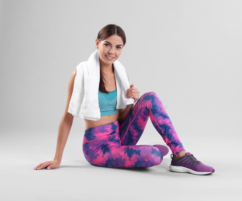 Jovem mulher bonita no sportswear com assento de toalha fotografia de stock royalty free
