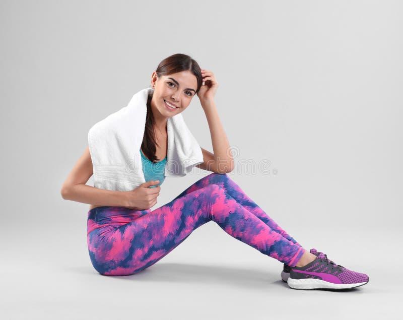 Jovem mulher bonita no sportswear com assento de toalha imagens de stock