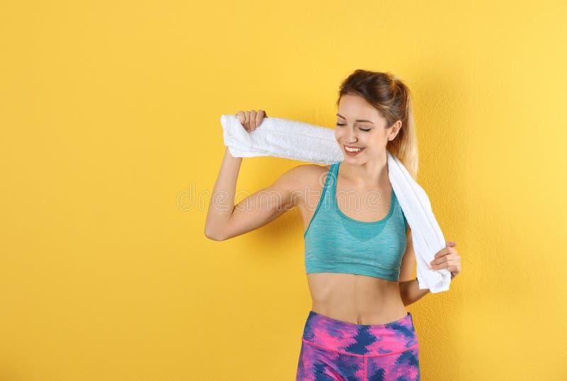Jovem mulher bonita no sportswear com a toalha no fundo da cor imagem de stock