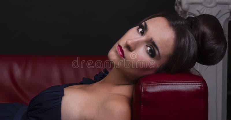 Jovem mulher bonita no vestido azul que encontra-se no sofá vermelho de couro fotos de stock