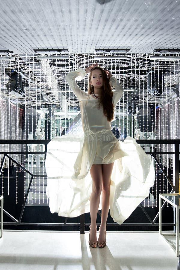 Jovem mulher bonita no vestido branco - clube nocturno imagens de stock royalty free
