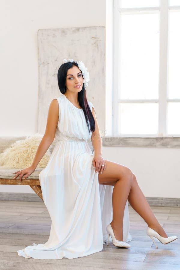 Jovem mulher bonita no vestido branco luxuoso tiro em um estúdio branco imagem de stock royalty free