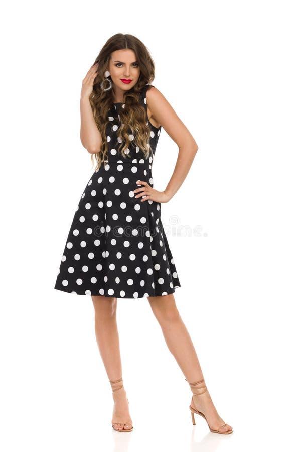 Jovem mulher bonita no vestido de cocktail preto em sandálias de Dots And Beige High Heels da polca fotografia de stock royalty free