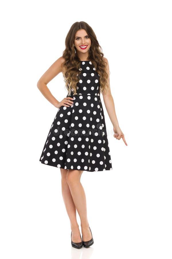 Jovem mulher bonita no vestido de cocktail preto na polca Dots And High Heels Is que aponta para baixo e que sorri foto de stock