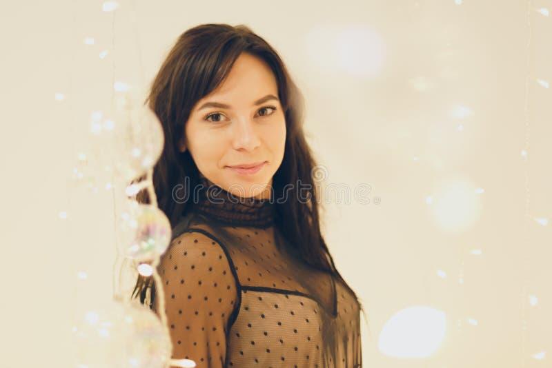 Jovem mulher bonita no vestido de cocktail que fica de sorriso sobre o fundo das luzes imagem de stock