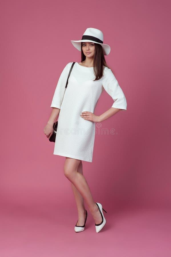 Jovem mulher bonita no vestido e no chapéu brancos elegantes do verão Menina que levanta em um fundo cor-de-rosa Foto da forma imagens de stock royalty free