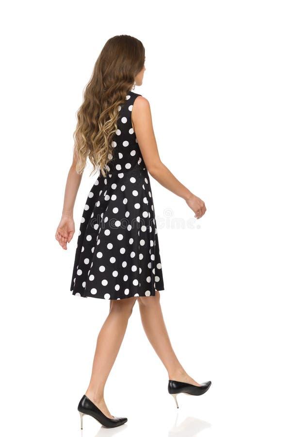 A jovem mulher bonita no vestido e nos saltos altos pontilhados pretos de cocktail está andando vista lateral traseira fotografia de stock